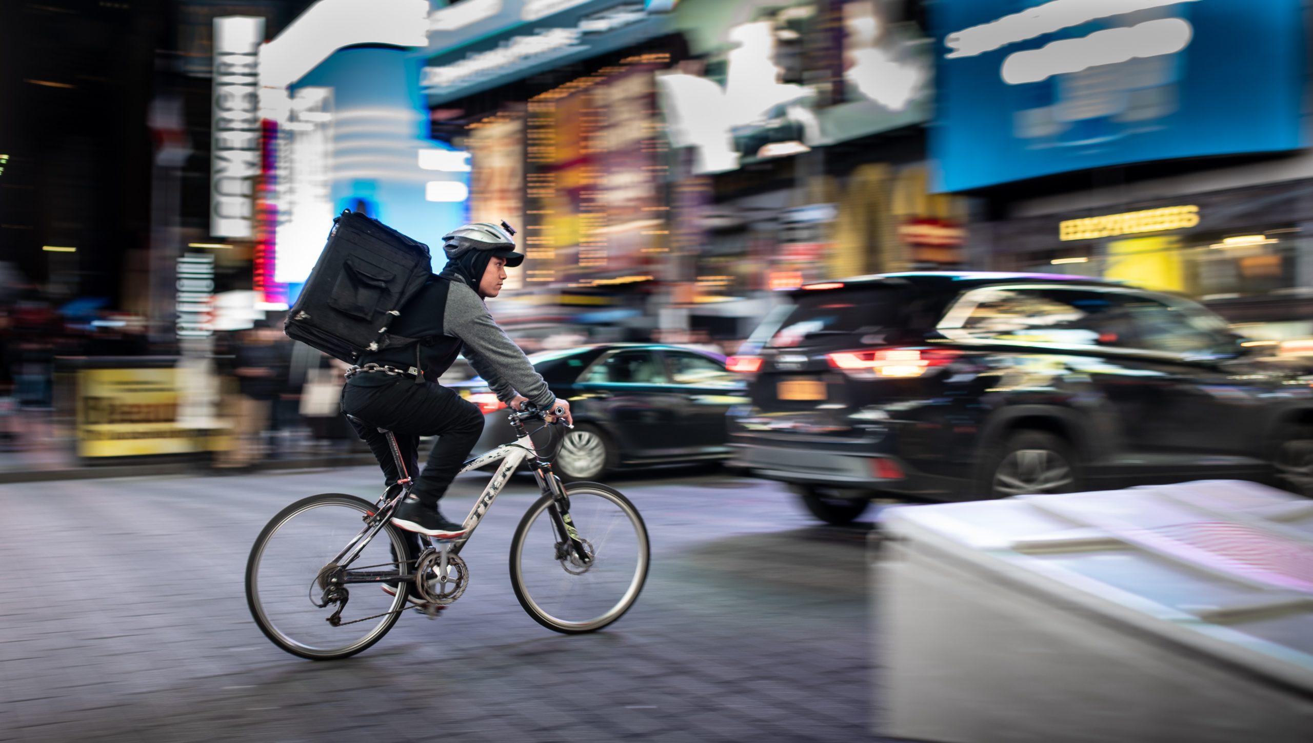 Vemos um homem fazendo delivery em uma cidade com sua bicicleta (imagem ilustrativa). Texto: franquia delivery.
