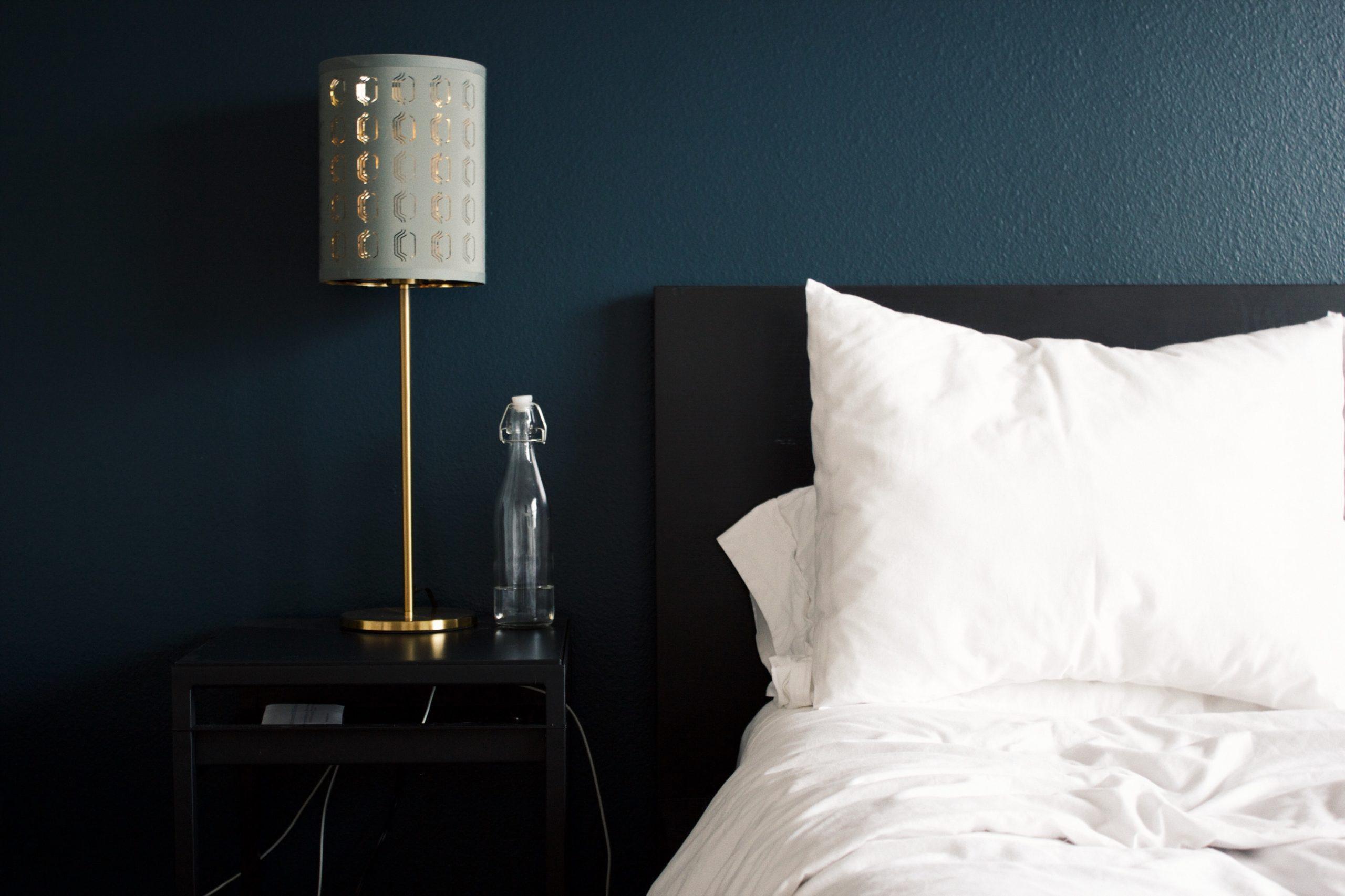 Vemos uma belíssima cama em um quarto de hotel; ao lado, sobre o móvel de cabeceira, temos uma garrafa de água e um abajur (imagem ilustrativa).