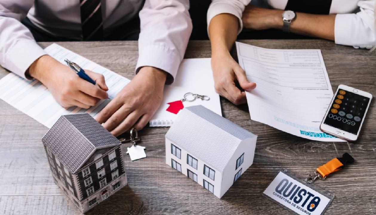 Vemos duas miniaturas de casa em uma mesa de escritório com pessoas trabalhando ao redor (imagem ilustrativa).