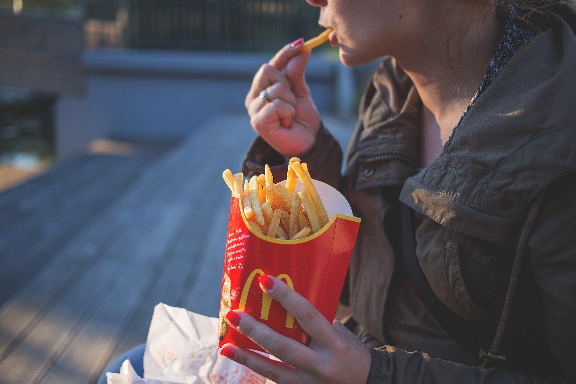 Vemos uma mulher de blusa de frio escura, segurando um pacote do McDonald's enquanto come uma batata frita (imagem ilustrativa). Texto: franquia do mcdonald's.