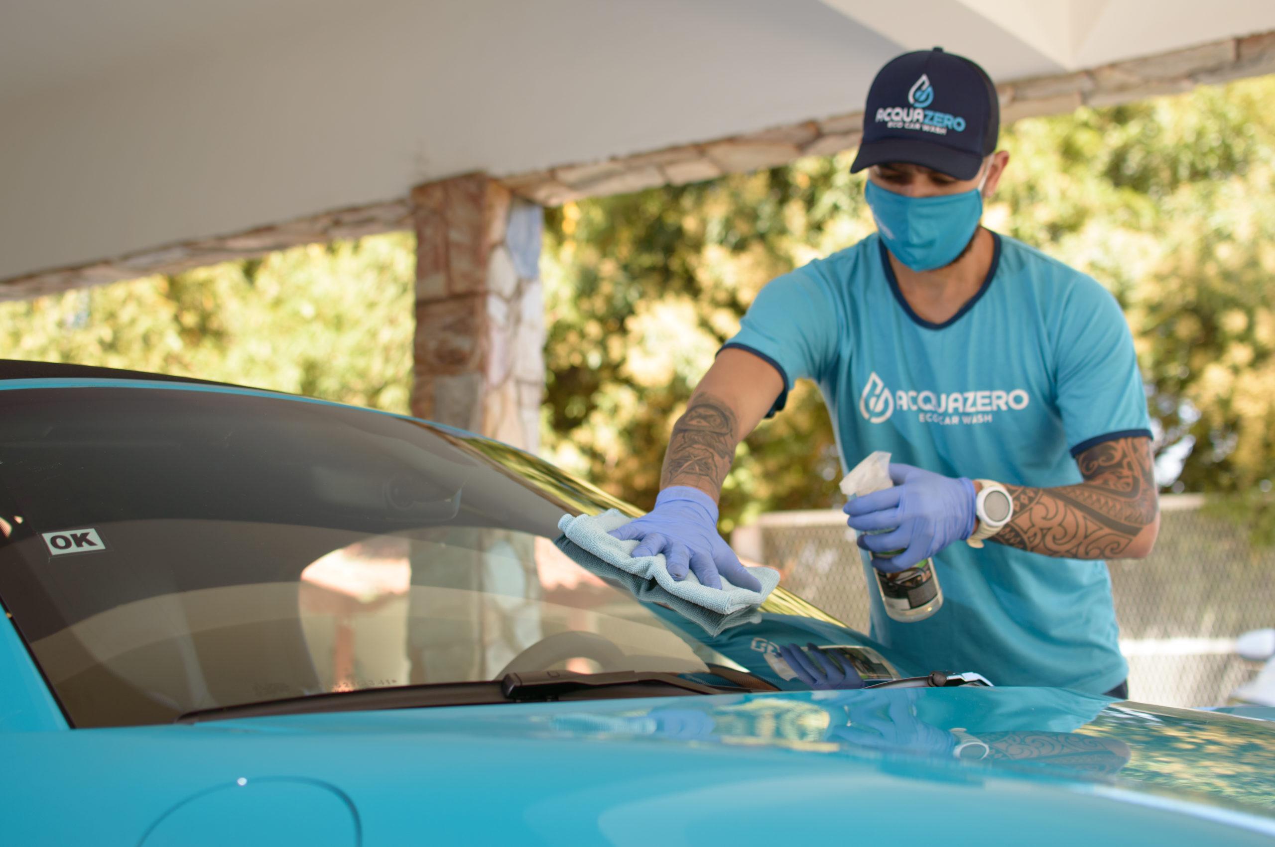 Vemos um técnico da Acquazero realizando a limpeza do para-brisa de um carro (imagem ilustrativa).