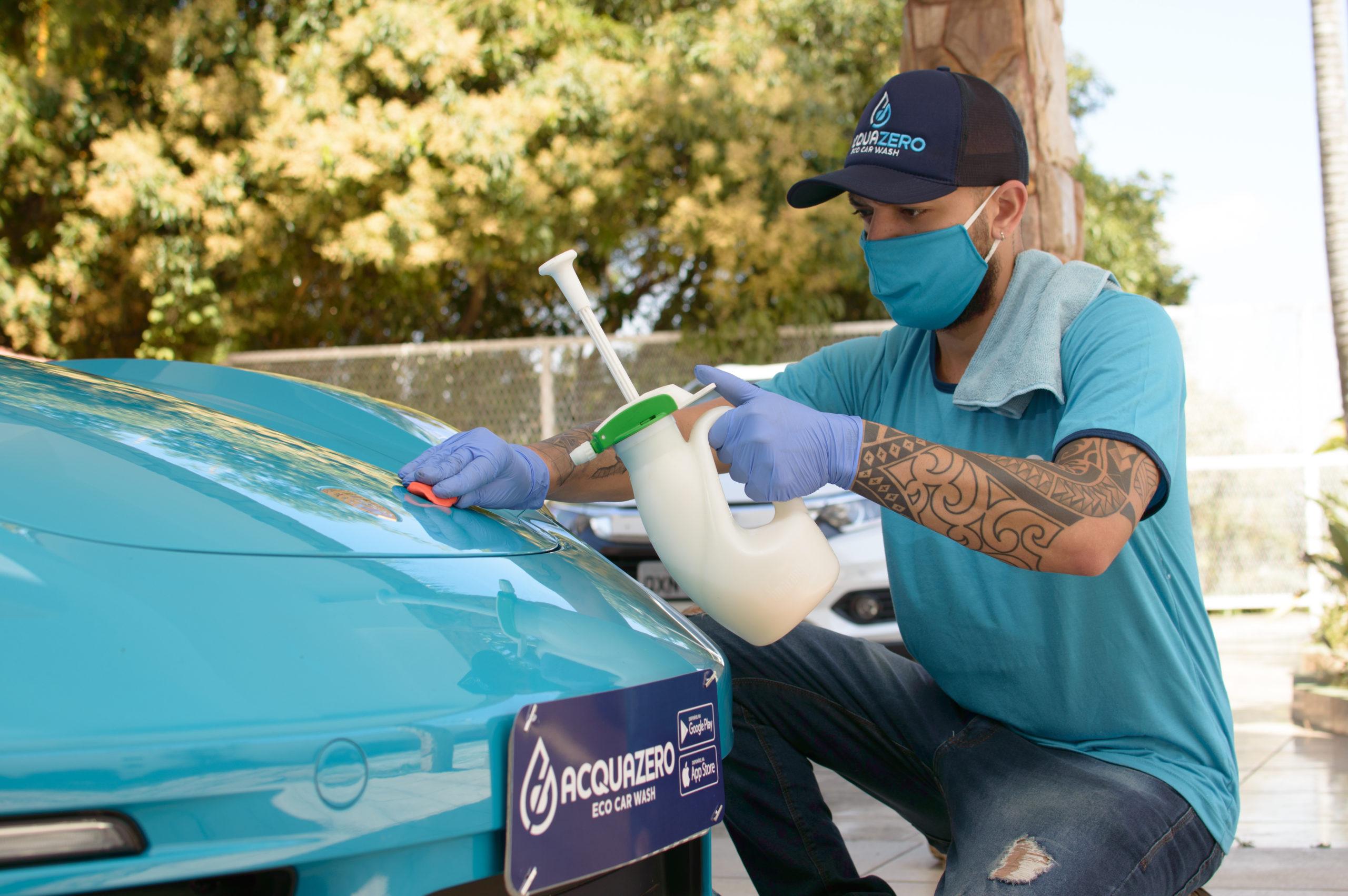 Vemos de um técnico da Acquazero devidamente paramentado, com máscara e luvas, limpando o capô de um carro azul (imagem ilustrativa). Texto: franquias com menos de 50 mil.