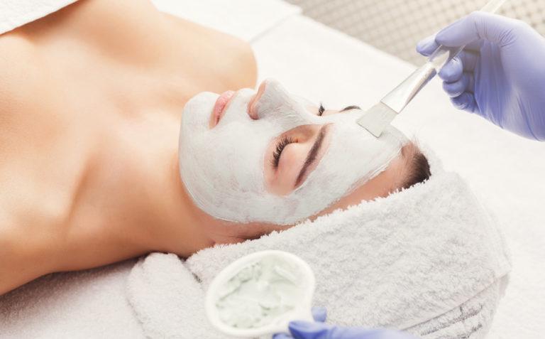 franquia beleza centro estética: mulher ganhando aplicação de mascara de argila