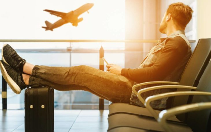 Imagem de uma pessoa no aeroporto olhando um avião decolar. Imagem ilustrativa texto franquia accorhotels.
