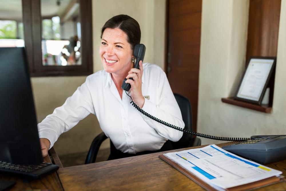 Vemos uma mulher sorridente, em um escritório, falando ao telefone (imagem ilustrativa). Texto: franquias mais lucrativas.