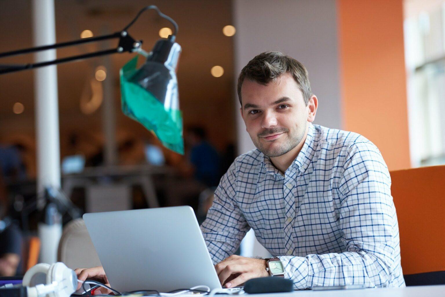 Vemos um empreendedor trabalhando em um computador (imagem ilustrativa). Texto: franquias mais lucrativas.