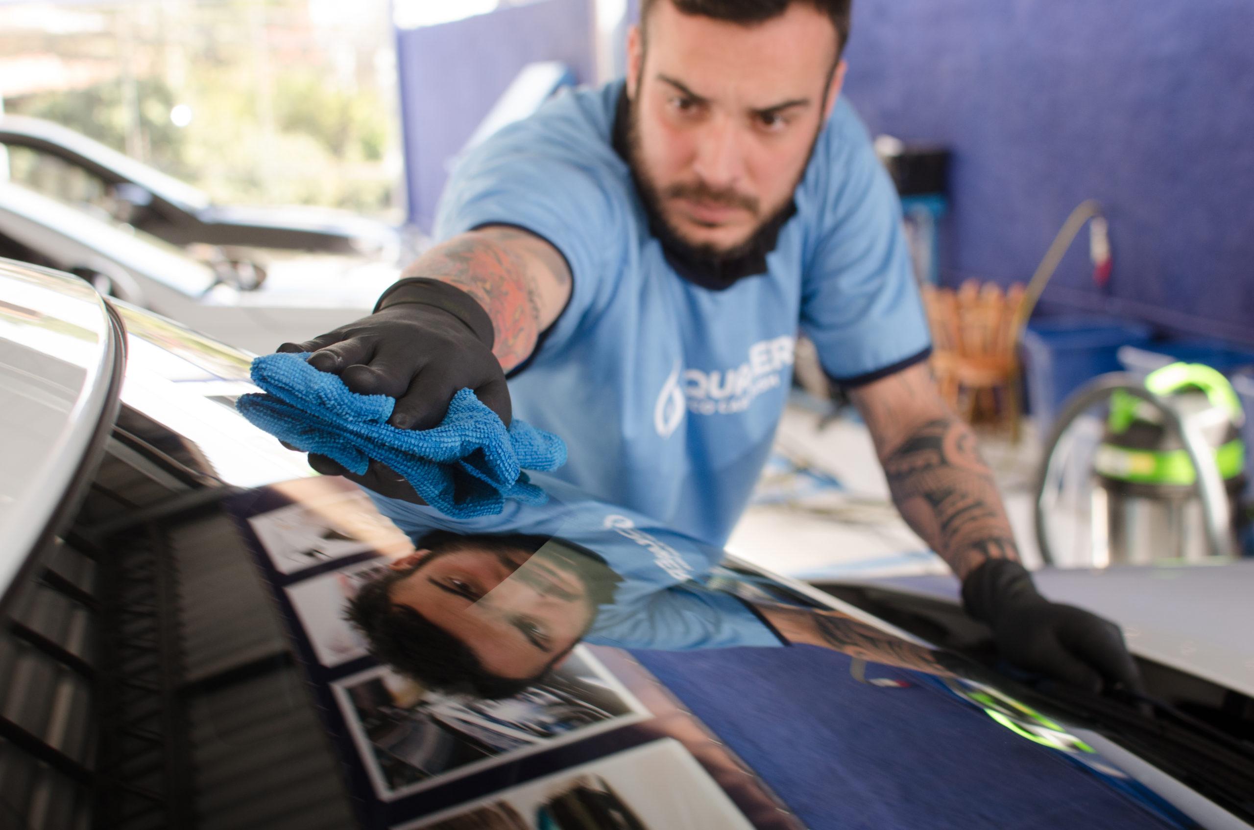 Vemos um técnico da franquia Acquazero realizando a limpeza do capô de um carro (imagem ilustrativa). Texto: ideias de empreendedorismo.