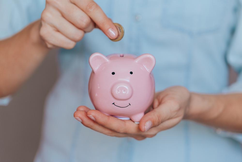 Vemos uma pessoa segurando um cofre no formato de porquinho rosa com uma moeda na mão (imagem ilustrativa). Texto: franquias boas e baratas 2021.