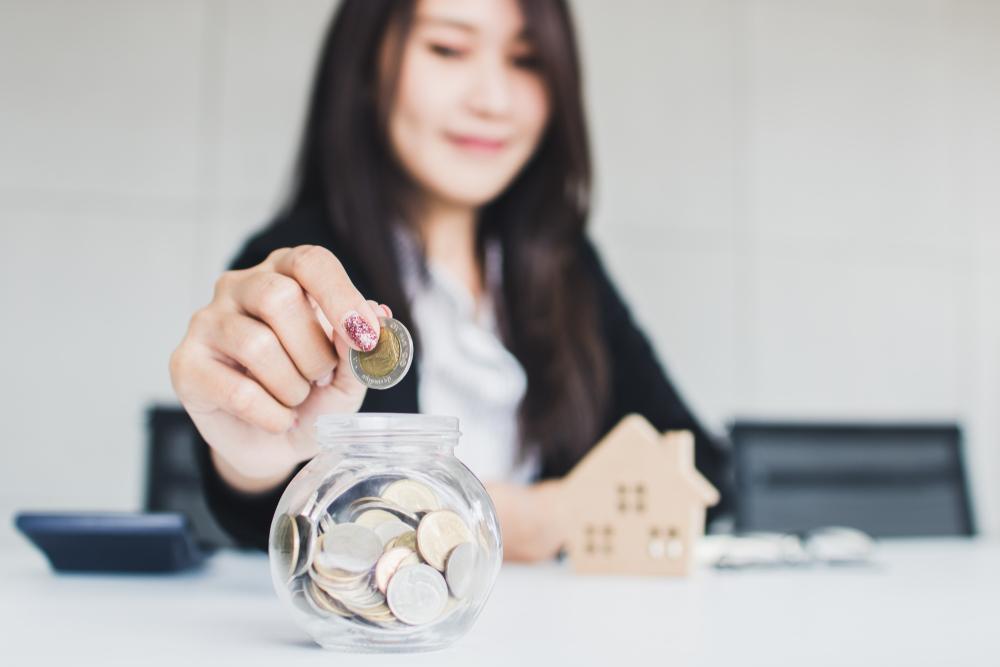 Mulher colocando moedas em um pote redondo. Imagem ilustrando texto como abrir um salão de beleza em um espaço pequeno.