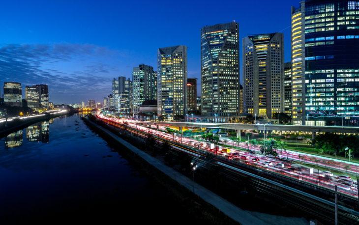 Imagem de uma grande avenida cheia de carros e vários prédios com as luzes acessas. Imagem ilustrativa texto feira de franquias.