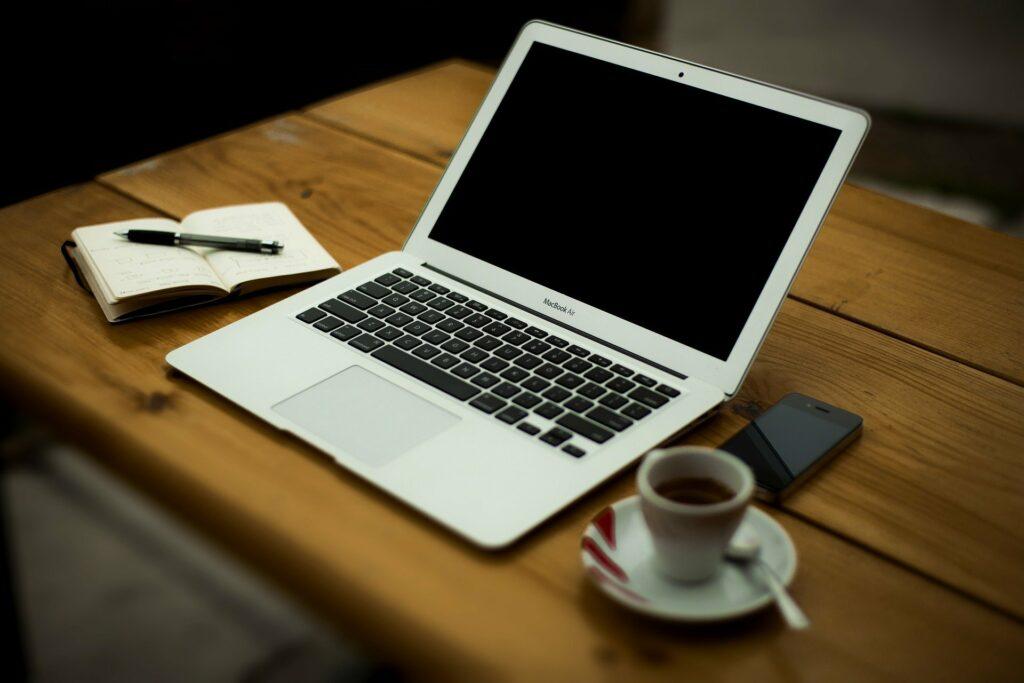 Imagem de uma mesa com um computador em cima, uma xícara de café de um lado e um caderno do outro.