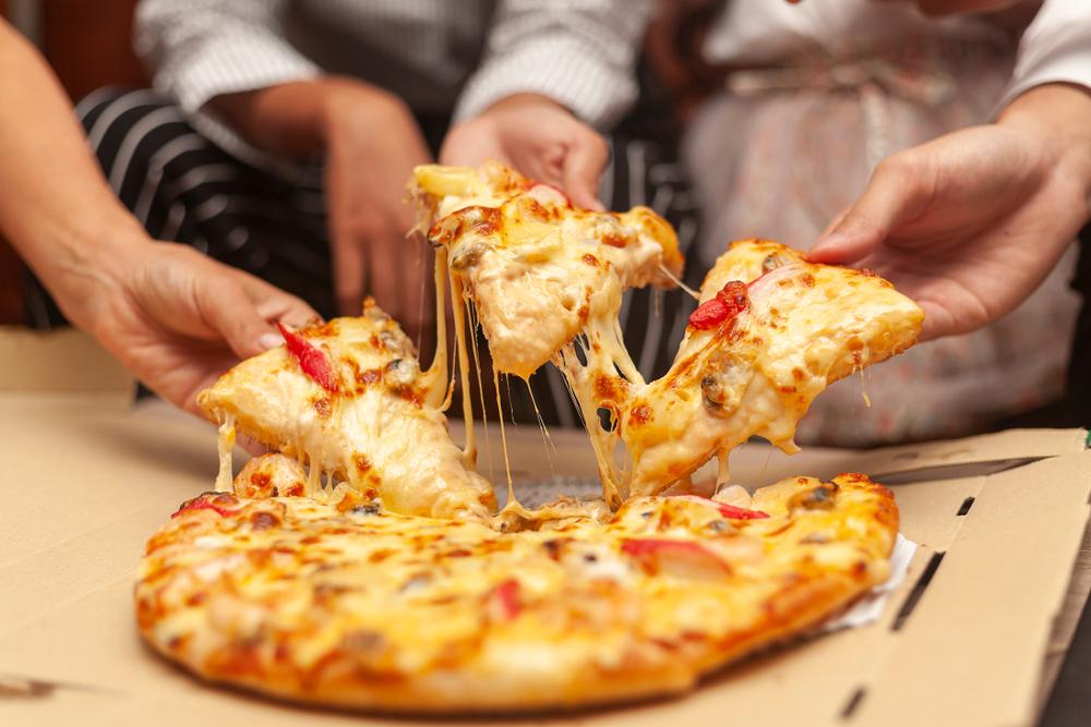Temos em perspectiva uma saborosa pizza. É possível notar uma roda de amigos. Vemos três mãos levantando, cada uma delas, uma fatia da pizza (imagem ilustrativa). Texto: como abrir uma pizzaria delivery.