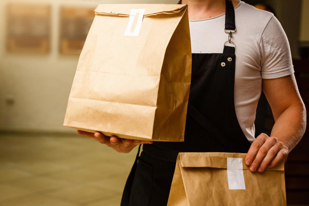 Vemos um homem segurando sacos de entrega (imagem ilustrativa). Texto: franquias Baratas 2021.
