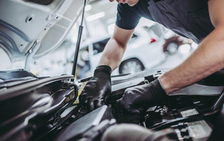Franquia de Oficina Mecânica: Homem fazendo manutenção no motor de um carro em sua oficina