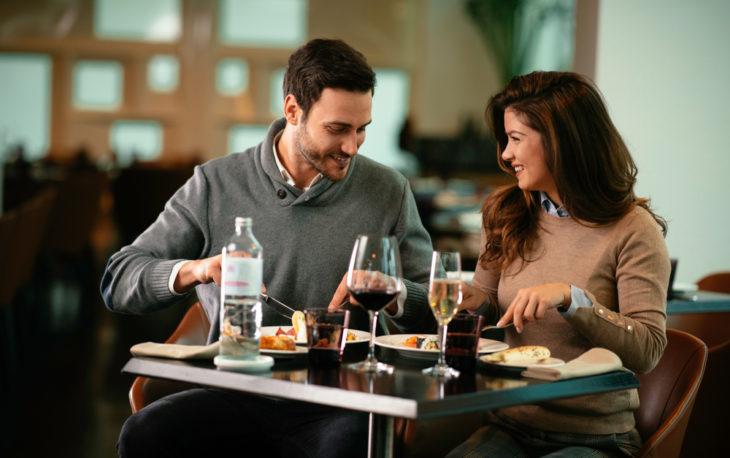 Franquia de restaurante: casal em uma mesa almoçando com vinho e água na mesa