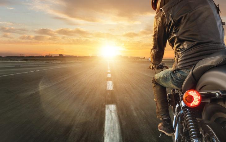 franquia de moto peças: homem viajando de moto com o por do sol ao final da estrada