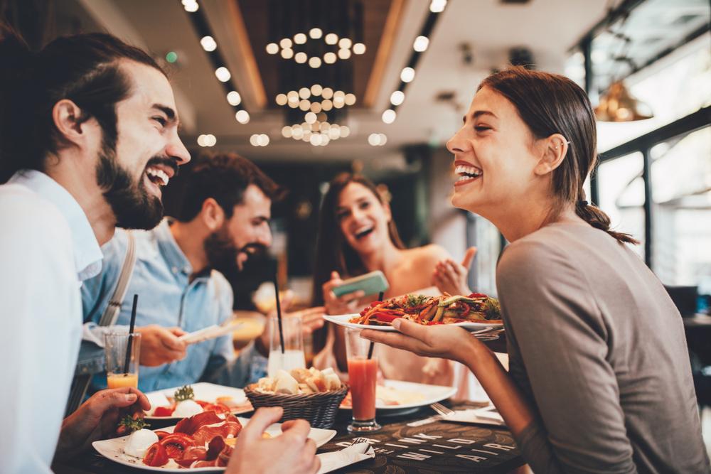 Vemos várias pessoas comendo em um restaurante e rindo (imagem ilustrativa).