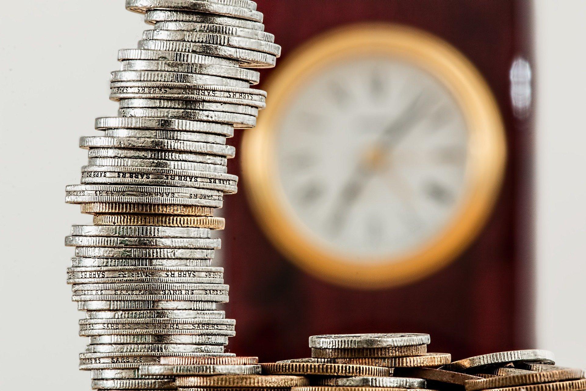 Vemos uma pilha de moedas e um relógio ao fundo (imagem ilustrativa). Texto: pegar empréstimo para abrir uma franquia.