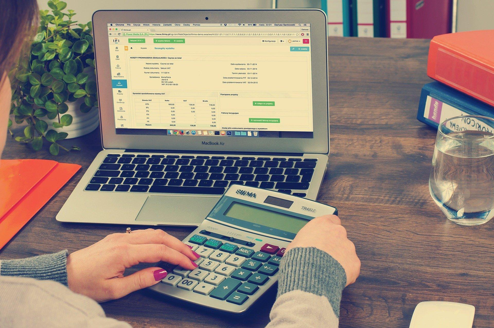 Vemos uma pessoa usando uma calculadora e um computador (imagem ilustrativa). Texto: pegar empréstimo para abrir uma franquia.