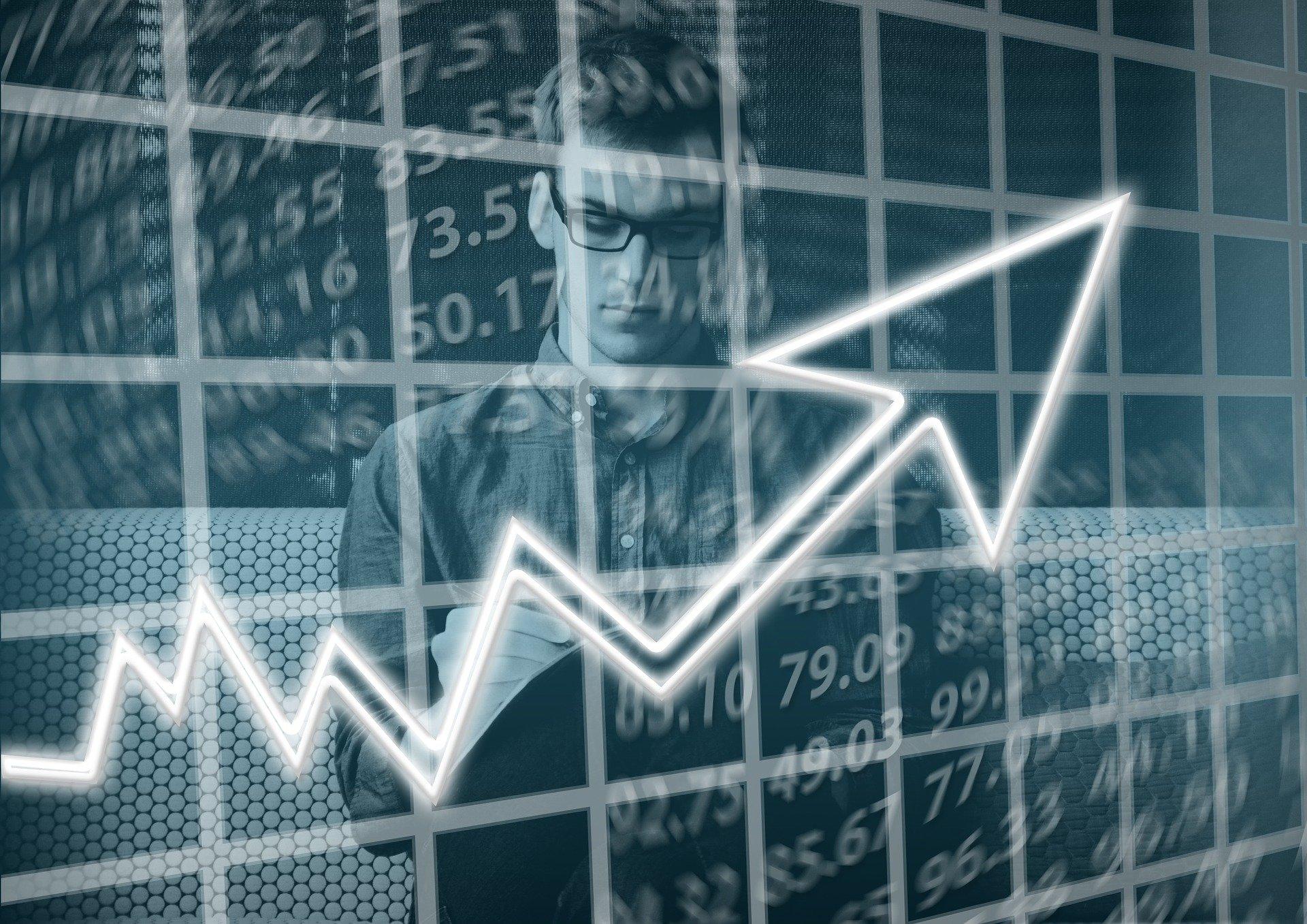 Vemos um empresário ao fundo e um gráfico em primeiro plano (imagem ilustrativa).
