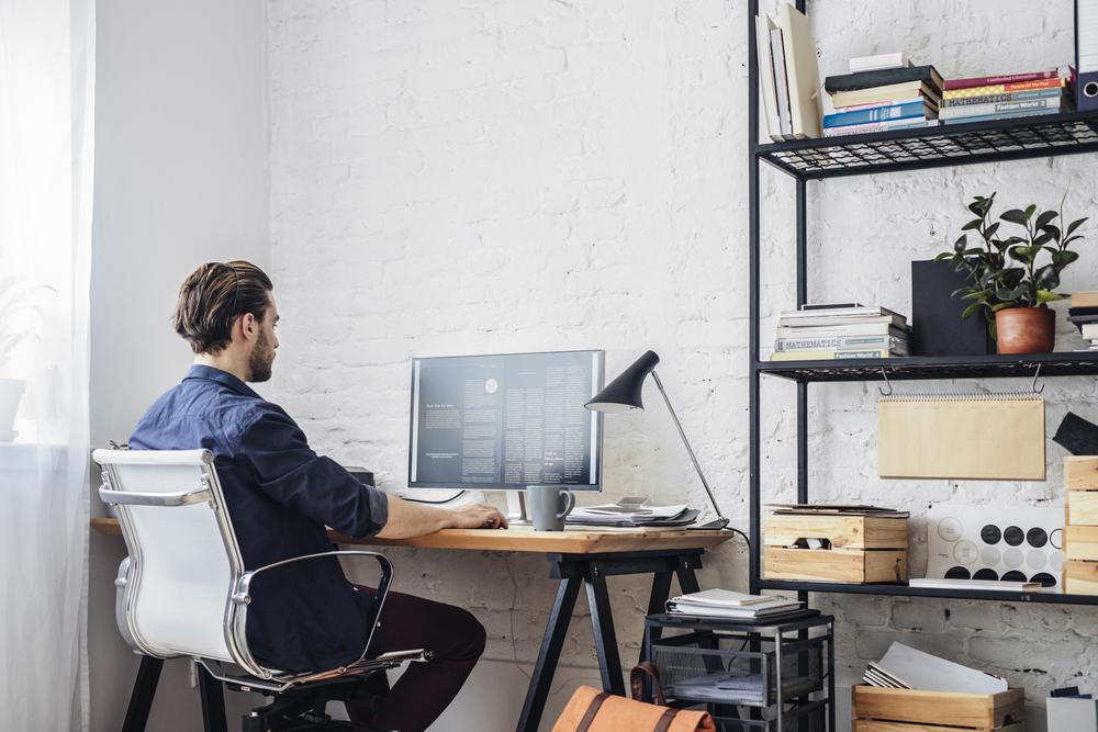 Vemos um homem trabalhando com um computador em sua casa (imagem ilustrativa). Texto: franquia touareg seguros.