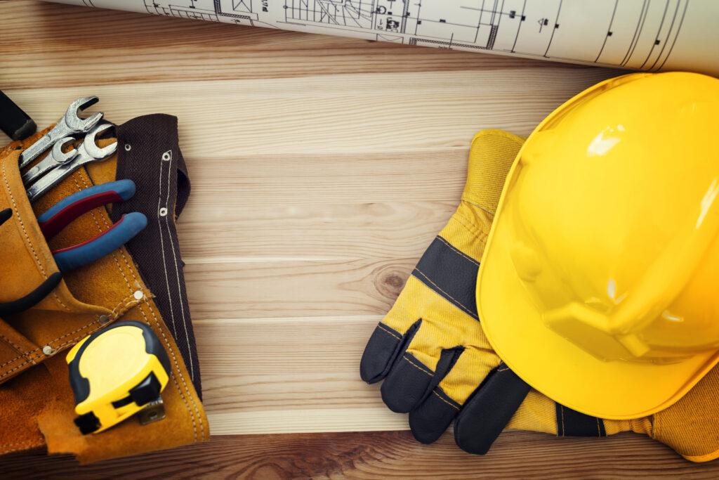 Imagens de ferramentas de construção e um capacete de pedreiro amarelo e luvas