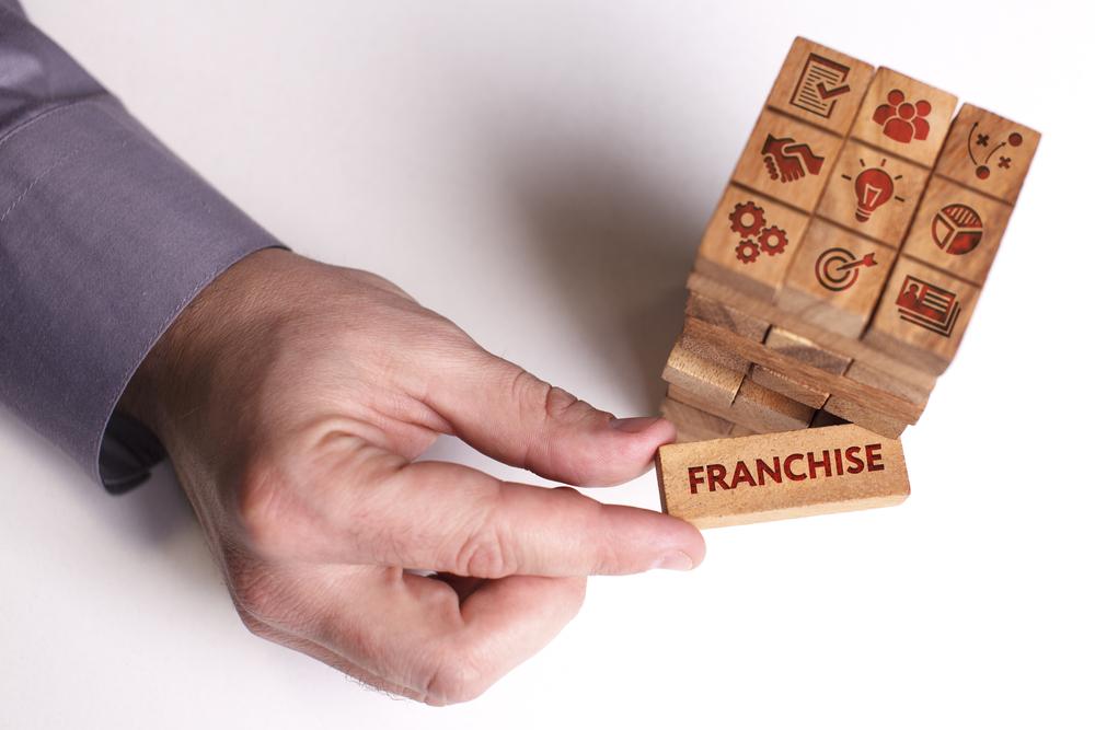 """Vemos algumas peças de madeira com ícones que remetem as franquias e investimentos. Vemos, ainda, a mão de um homem que retira desse conjunto uma peça escrito """"franchise"""" (imagem ilustrativa). Texto: franquias baratas e lucrativas para cidades pequenas."""