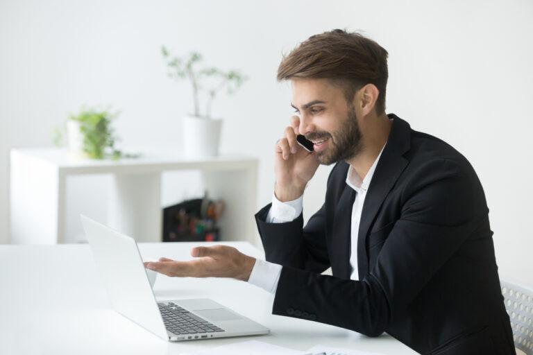 Homem conversando no telefone e olhando para a tela do seu notebook. Imagem ilustrativa texto seguralta