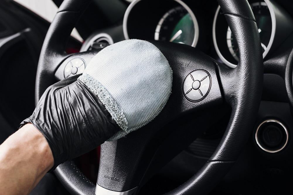 Mão de uma pessoa com luva preta segurando uma esponja azul enquanto realiza a limpeza de um volante preto (imagem ilustrativa). Texto: flipwash.