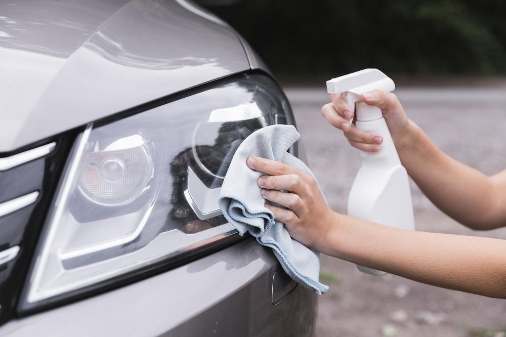 Foto de uma mão segurando uma toalha azul, enquanto a outra segura um borrifador branco e limpa o farol direito de um carro prata.