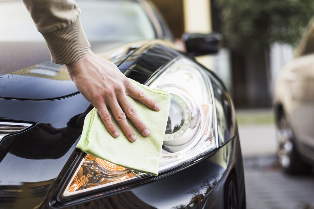 Foto de uma mão, segurando um lenço verde enquanto limpa a parte do farol direito de um carro preto. Ao fundo vemos uma rua. Imagem ilustrativa para texto flipwash.