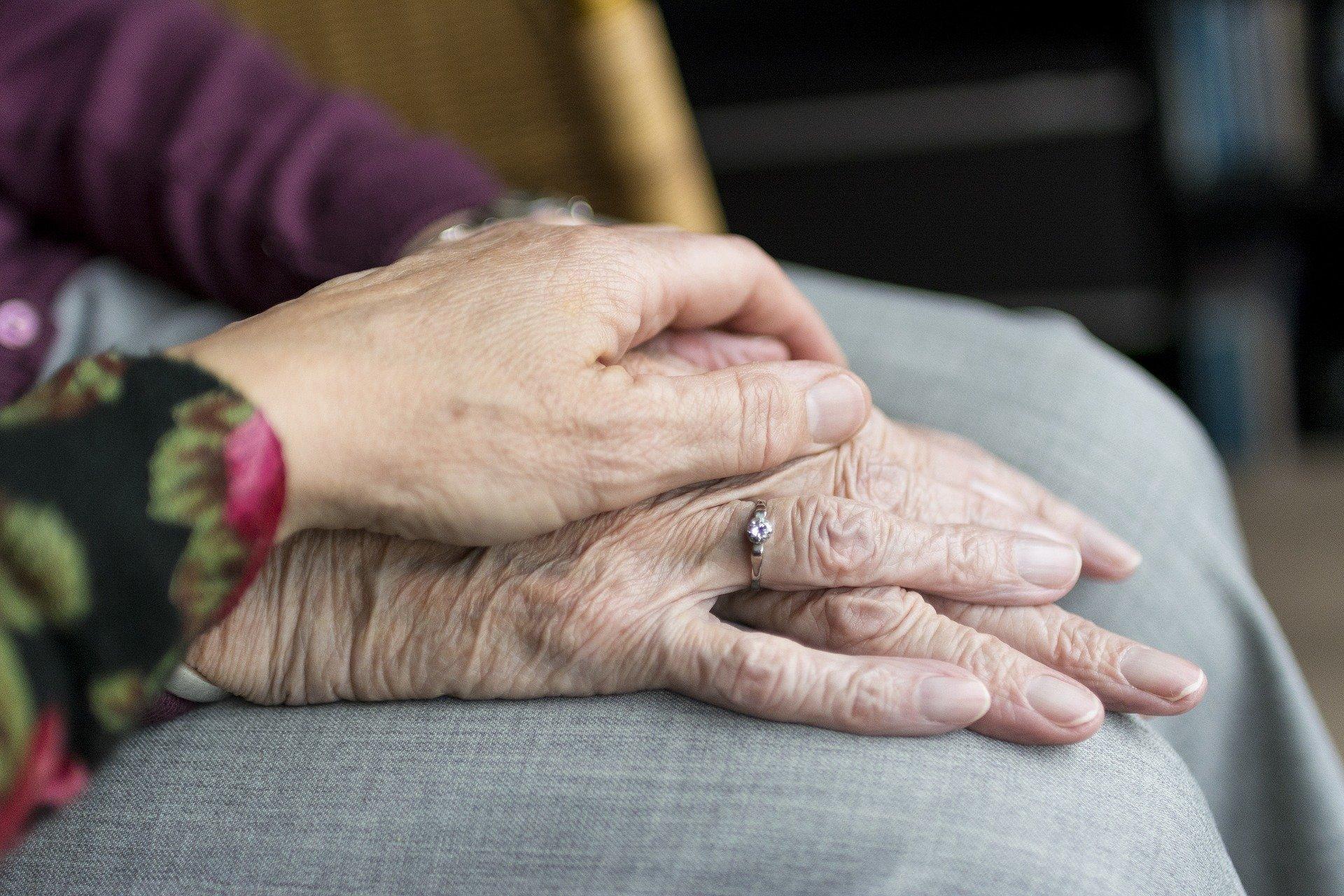 Mão de uma pessoa mais nova, segurando as mãos de uma idosa (imagem ilustrativa).