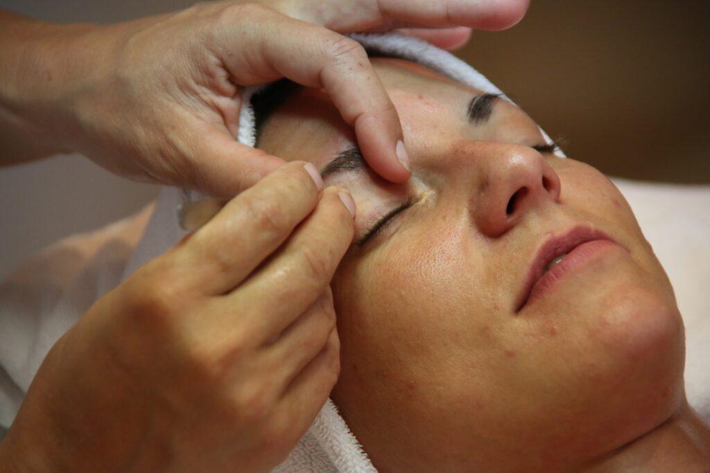foto de uma pessoa fazendo a sobrancelha de uma cliente.