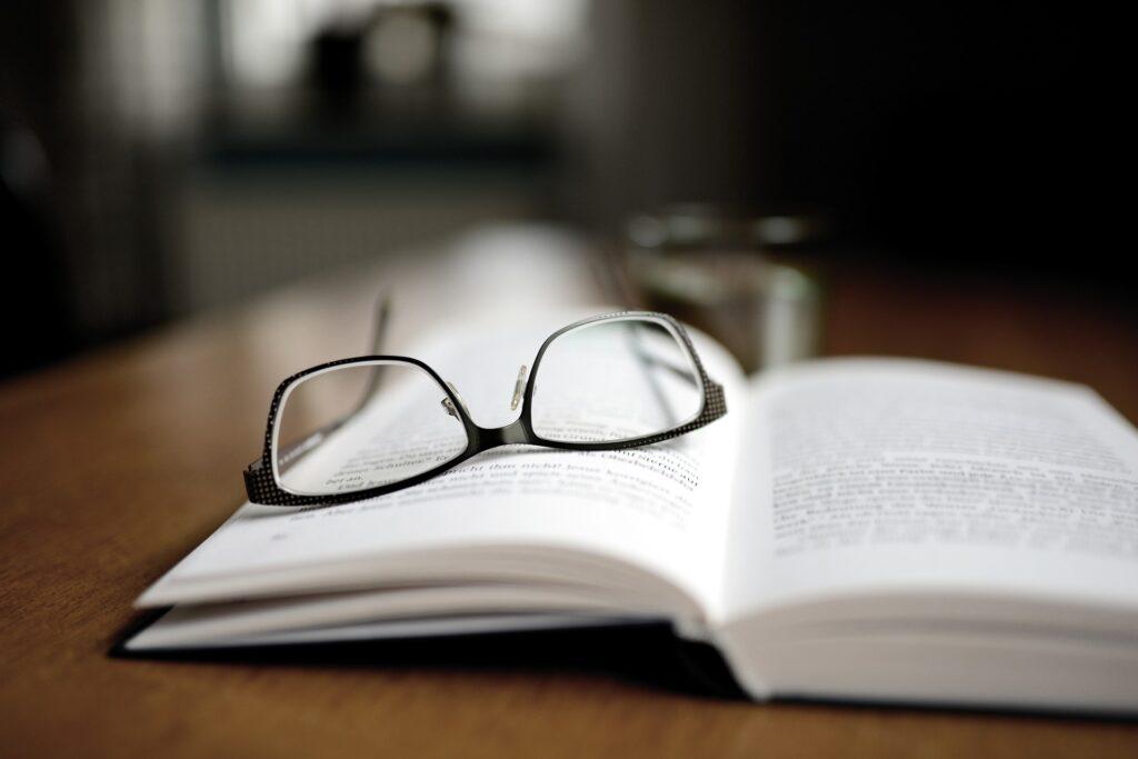 Vemos um óculos em cima de um caderno, em uma mesa de madeira (imagem ilustrativa). Texto: Franquia ideal para cidade pequena de 5 mil habitantes.