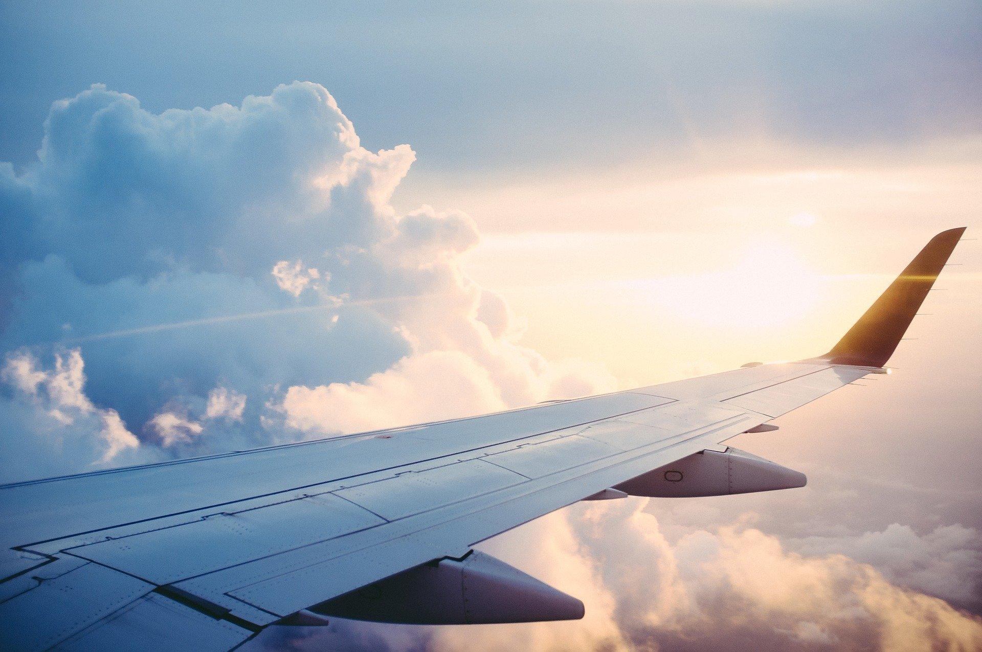 Foto da asa de um avião com o céu ao fundo (imagem ilustrativa). Texto: Franquia ideal para cidade pequena de 5 mil habitantes.