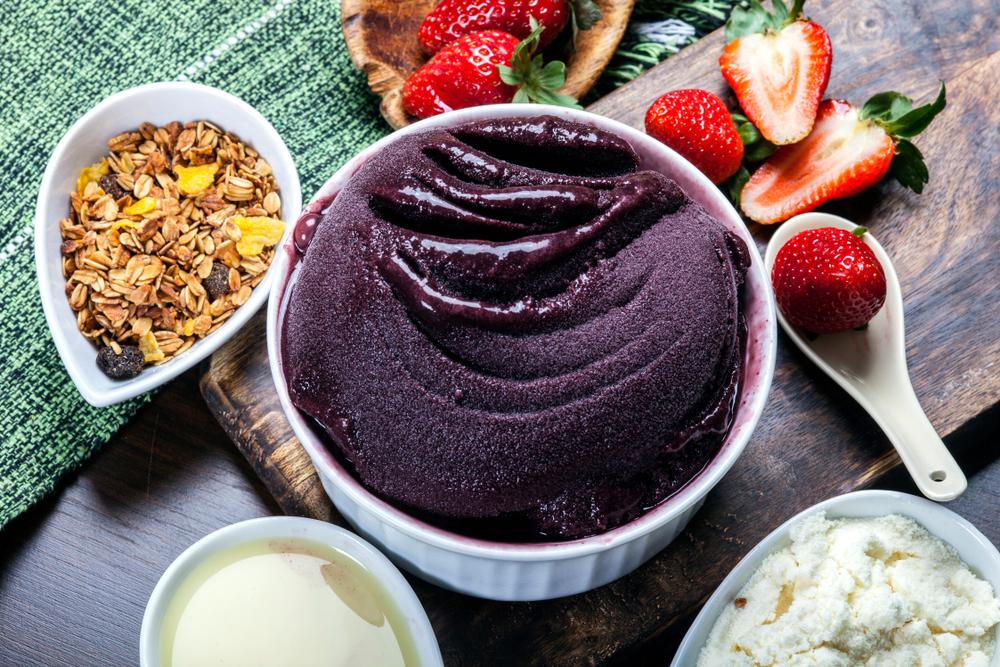 Vemos uma tigela de açaí com acompanhamentos – morango, leite condensado, leite em pó e granola – ao lado (imagem ilustrativa).