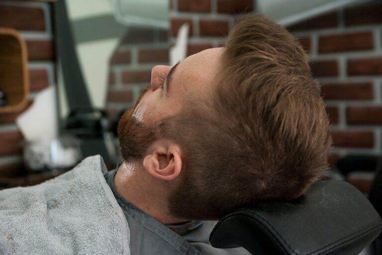 Foto de um homem deitado em uma cadeira de barbaria, com uma parede de tijolos ao fundo. Imagem ilustrativa para texto franquia de barbearia.
