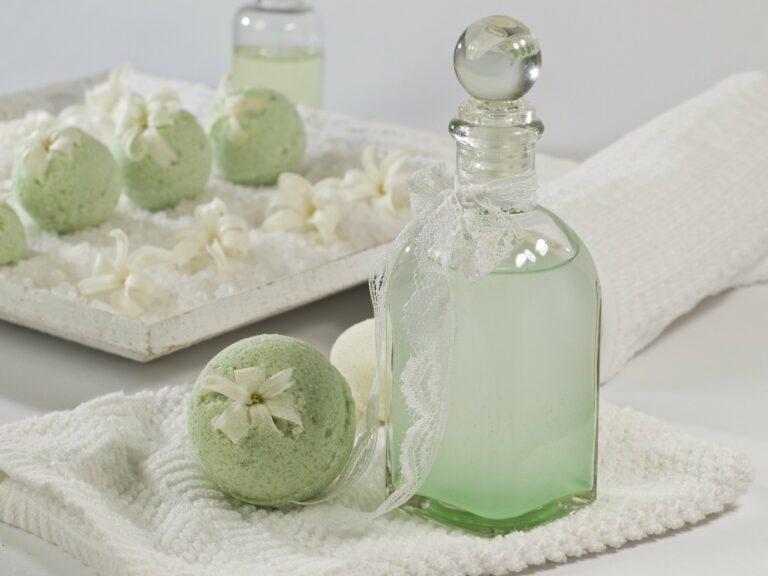 Vidro com produtos para banho verde, além de bolinhas de sabão também verdes. Vemos um prato claro ao fundo e uma toalha clara sobre o local. Imagem ilustrativa para texto franquia natura.