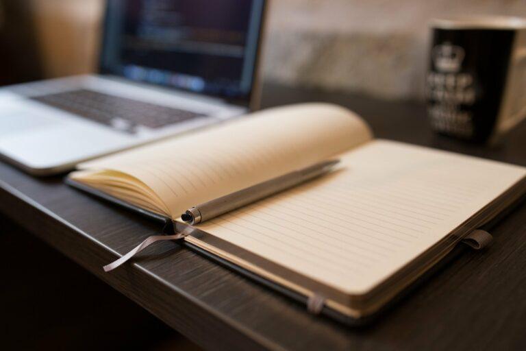 Foto de um caderno com uma caneta, ao lado de um computador em uma mesa marrom. Imagem ilustrativa para texto como começar um negócio.