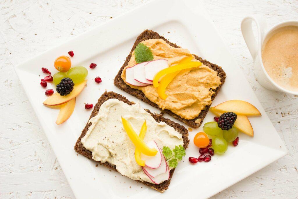 mesa branca com um prato branco com comidas saudáveis, torrada e frutas. ao lado temos uma xícara de café. Imagem ilustrativa para texto negócios com pouco investimento e retorno rápido.