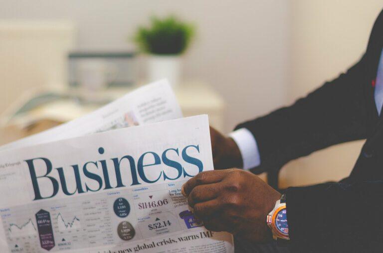 Foto de um homem com roupa social segurando um jornal sobre negócios, ao fundo vemos um vaso com plantas. Imagem ilustrativa para texto abf franquias.