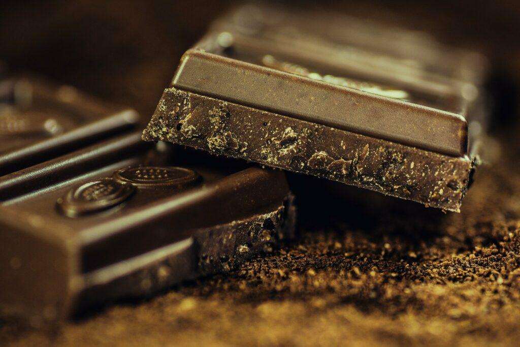 Foto de duas barras de chocolate pela metade em uma superfície marrom. Imagem ilustrativa para texto kopenhagen.