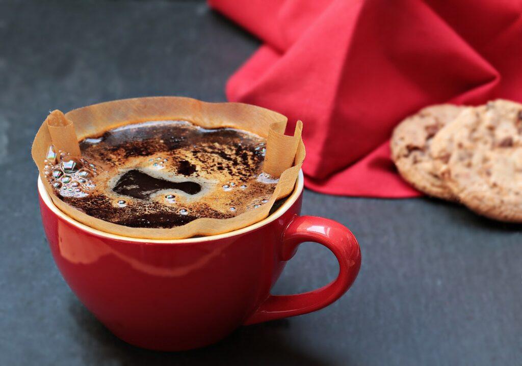Foto de uma xícara vermelha com café em uma superfície preta, ao fundo vemos um pano vermelho e cookies.