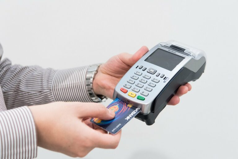 Duas mãos segurando uma máquina de cartão de crédito cinza enquanto utiliza um cartão de crédito azul. Temos uma fundo branco. Imagem ilustrativa para texto franquia de maquininha de cartão.
