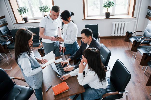 Vemos vários empresários reunidos ao redor de uma mesa em um escritório (imagem ilustrativa). Texto: como abrir uma pizzaria delivery.