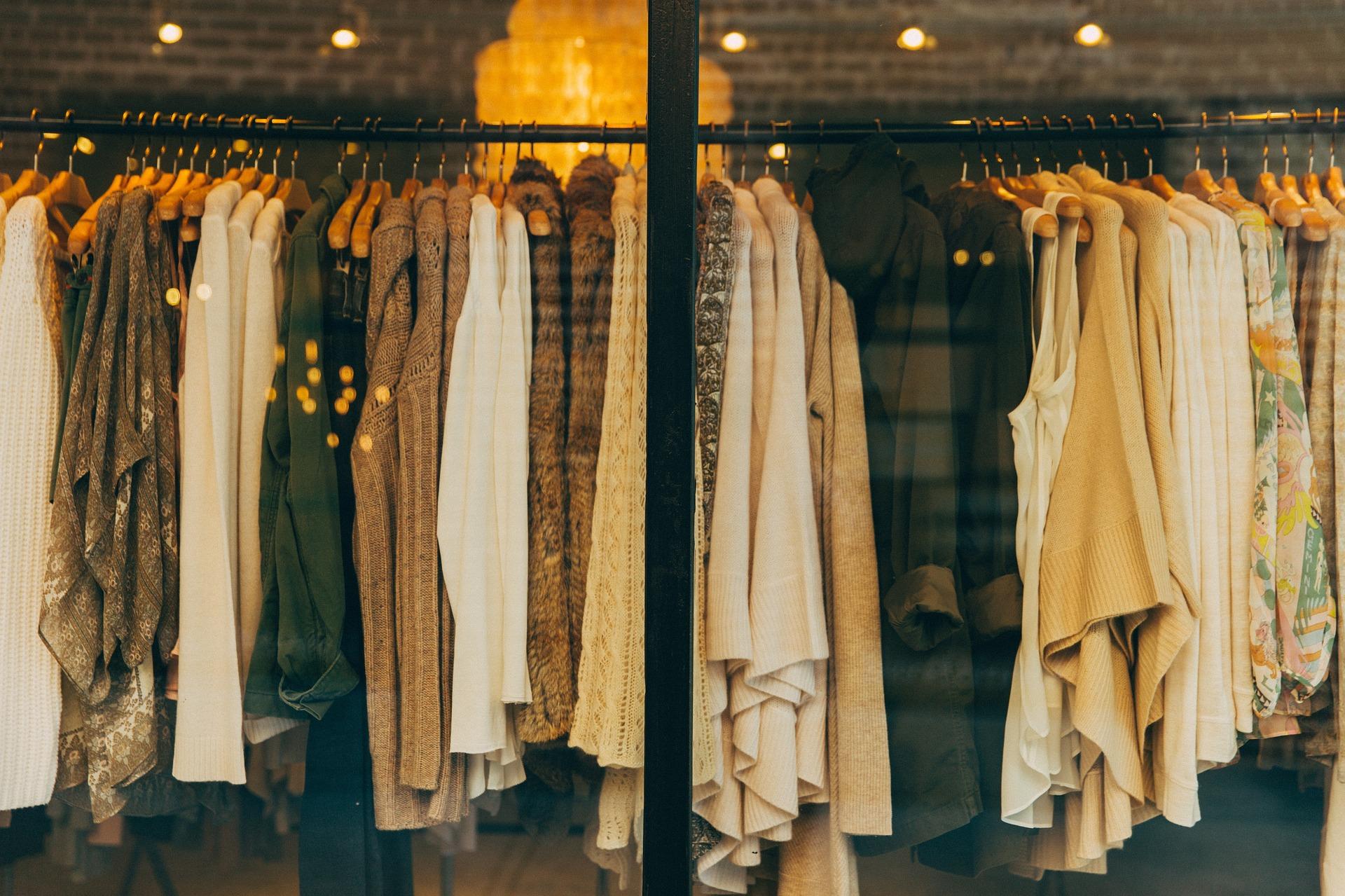 Foto lateral de uma vitrine de loja, com várias roupas em um cabide. As cores variam entre branco, bege, preto, amarelo. Ao fundo vemos algumas luminárias no interior da loja. Imagem ilustrativa para texto franquia hering.