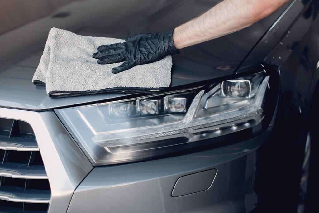 Homem faz o polimento do capo de um carro cinza (imagem ilustrativa). Texto: franquia Freewet.