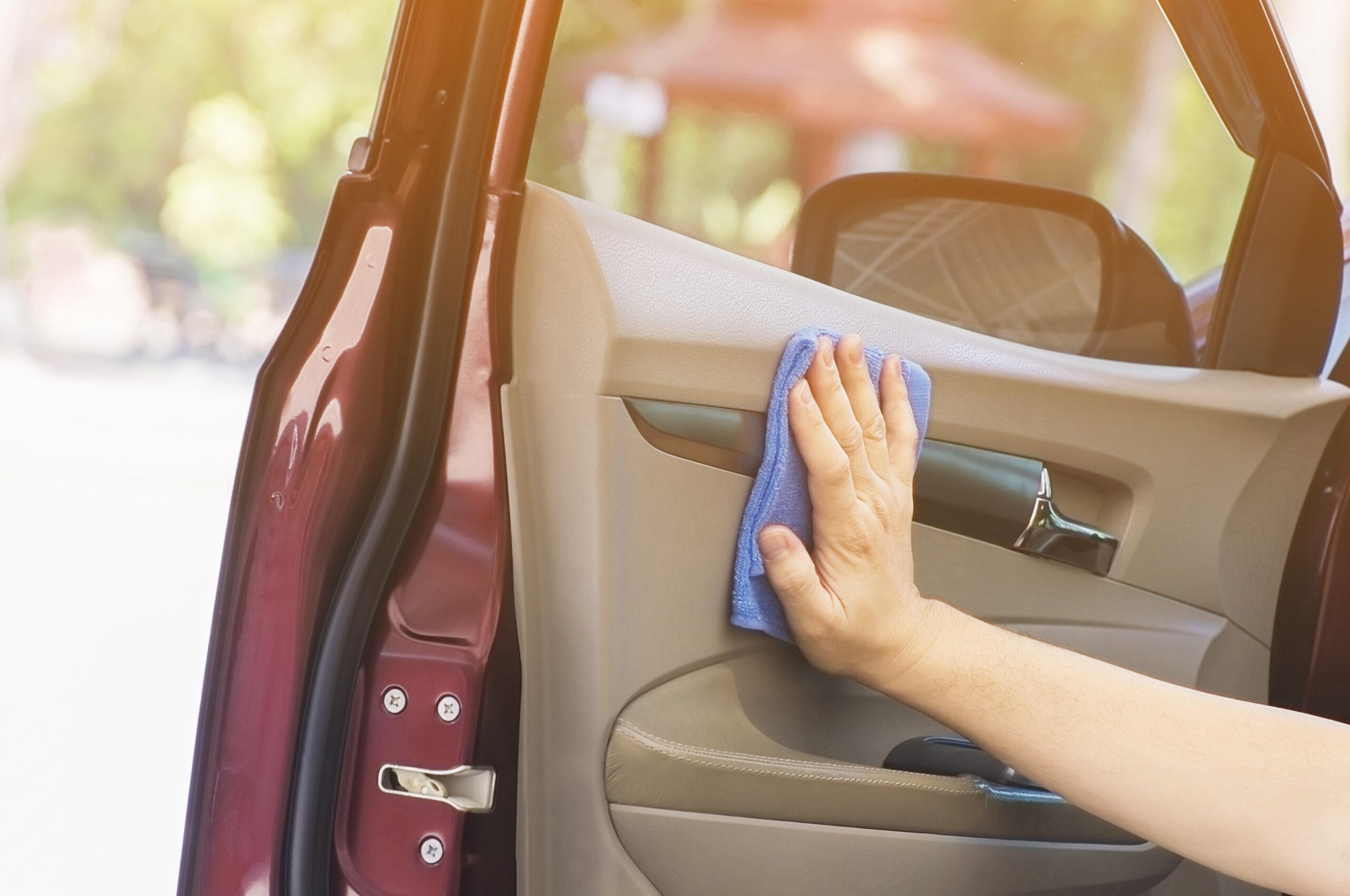 Imagem de uma mão limpando a porta de um carro por dentro. Imagem ilustrativa texto franquia freewet