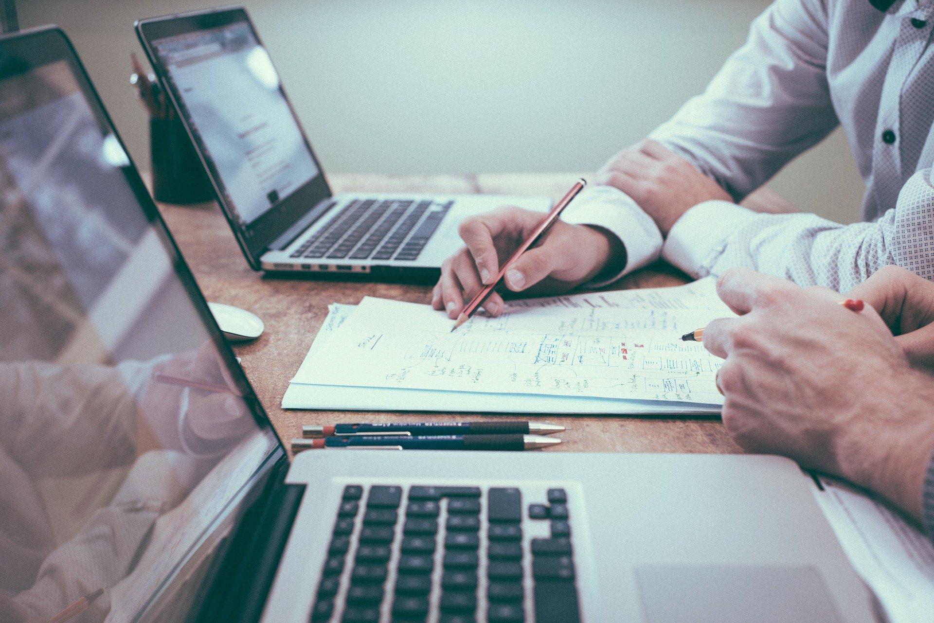Foto de duas pessoas em uma mesa olhando papeis e com dois computadores abertos. Imagem ilustrativa para texto montar um negócio.