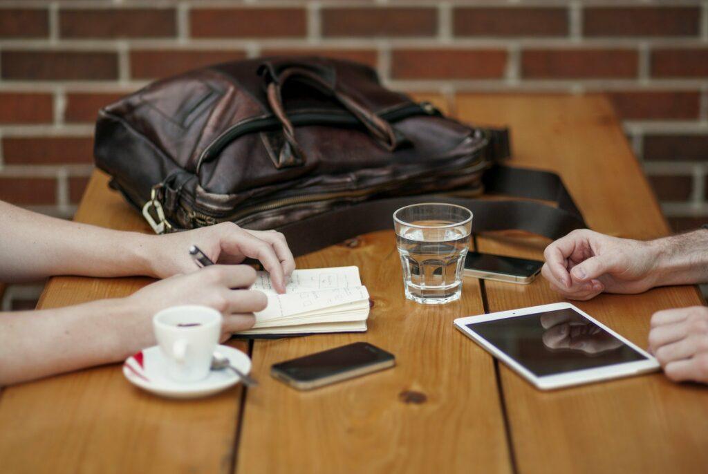 duas pessoas em uma mesa de madeira, vemos uma bolsa de couro, um copo, uma xícara, celulares e tablet, além de um caderno.